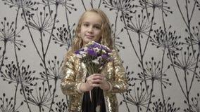 La niña bonita sostiene las flores en manos metrajes