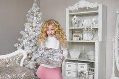 La niña bonita sostiene una caja de regalo en las manos en un estudio ligero de la decoración del Año Nuevo Fotografía de archivo libre de regalías