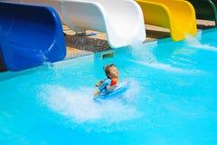 La niña cae en la piscina con las diapositivas de agua Fotos de archivo