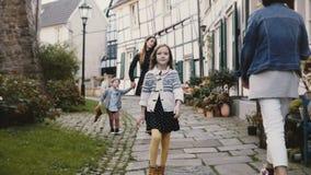 La niña camina a la cámara, relajado y a la sonrisa Madre europea así como dos niños La media madera contiene Alemania 4K almacen de video