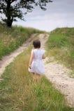 La niña camina descalzo a lo largo del camino imagen de archivo libre de regalías