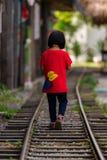 La niña camina en el ferrocarril Foto de archivo libre de regalías