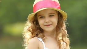 La niña camina en el parque que mira en la distancia y los sueños Cámara lenta metrajes