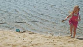 La niña camina en la playa por el río con un perro almacen de video