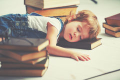 La niña cansada se cayó dormido para los libros foto de archivo