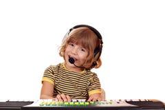 La niña canta y juega el teclado Foto de archivo