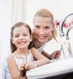 La niña cepilla los dientes con su mamá imagenes de archivo