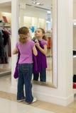 La niña cerca de un espejo intenta encendido la ropa en una tienda Fotografía de archivo libre de regalías