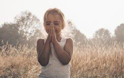 La niña la cerró los ojos que rogaba en la puesta del sol Las manos doblaron en el concepto del rezo para la fe, la espiritualida foto de archivo libre de regalías
