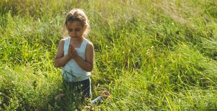 La niña la cerró los ojos que rogaba en la puesta del sol Las manos doblaron en el concepto del rezo para la fe, la espiritualida fotos de archivo