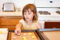La niña coloca la pasta de la galleta en la bandeja del horno Foto de archivo libre de regalías