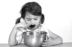 La niña come la crema del chocolate Foto de archivo libre de regalías