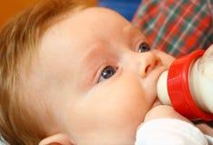 La niña come la leche Foto de archivo