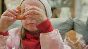 La niña come los anillos de espuma deliciosos en el café almacen de metraje de vídeo