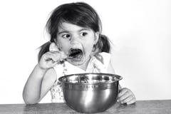 La niña come porciones de crema del chocolate Fotografía de archivo libre de regalías