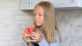 La niña come la sandía en la cocina almacen de metraje de vídeo