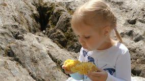 La niña come un maíz hervido almacen de video