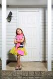La niña con el bolso se coloca en el pórtico blanco de la casa Imágenes de archivo libres de regalías
