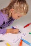 La niña con el pelo rubio drena Foto de archivo libre de regalías