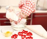 La niña con el sombrero del cocinero puso la harina Foto de archivo
