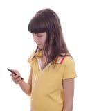 La niña con el teléfono móvil. Imagen de archivo libre de regalías