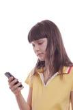 La niña con el teléfono móvil. Imagenes de archivo
