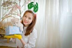 La niña con invierno viste sostener la caja de regalo de la Navidad, Fotografía de archivo