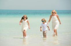 La niña con la familia se divierte en la playa Foto de archivo libre de regalías