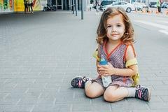 La niña con la mochila y el biberón viajan en el aeropuerto o el ferrocarril, niños viaja fotos de archivo libres de regalías
