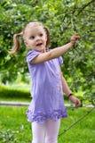 La niña con las coletas en el asombro mira manzanas en un salvado fotografía de archivo