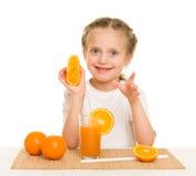 La niña con las frutas y verduras hace el jugo Imagen de archivo