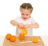 La niña con las frutas y verduras hace el jugo Foto de archivo libre de regalías