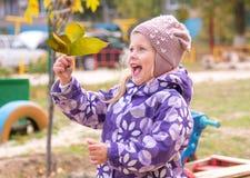 La niña con las hojas de las demostraciones del entusiasmo Fotografía de archivo libre de regalías