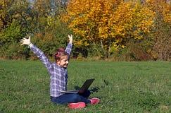 La niña con las manos sube y un ordenador portátil en el otoño del parque Fotografía de archivo