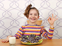 La niña con los anillos de espuma del chocolate y la mano aceptable firman Fotografía de archivo libre de regalías