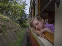 La niña con los ojos soñadores viaja en el tren foto de archivo