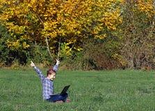 La niña con los pulgares sube y un ordenador portátil en el otoño del parque Foto de archivo