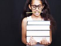 La niña con los vidrios y el lápiz sostiene los libros Imagen de archivo libre de regalías