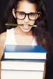 La niña con los vidrios y el lápiz sostiene los libros Fotografía de archivo libre de regalías