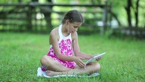 La niña con PC de la tableta se sienta en la hierba en jardín metrajes