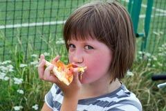 La niña con placer come una pizza en el parque imagen de archivo libre de regalías