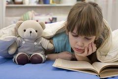La niña con refiere el sofá Imagen de archivo libre de regalías