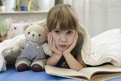 La niña con refiere el sofá Imagenes de archivo