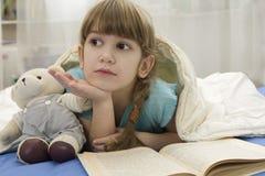 La niña con refiere el sofá Fotos de archivo libres de regalías