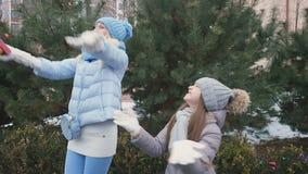 La niña con su madre disfruta un pequeño confeti al aire libre cerca de abeto metrajes