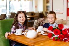 La niña con un bebé, sentándose en la tabla y bebió té con la torta foto de archivo libre de regalías