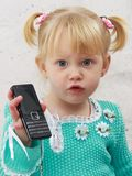 La niña con un teléfono móvil Fotografía de archivo
