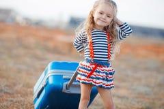 La niña con una maleta azul grande Imagenes de archivo