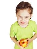 La niña con una manzana roja grande mira hacia arriba Fotografía de archivo libre de regalías