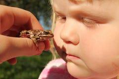 La niña consigue conocida con la fauna - rana salvaje fotos de archivo libres de regalías